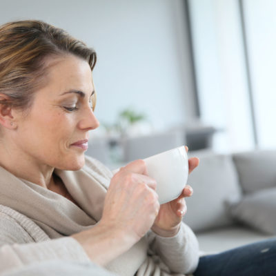 mature woman in sofa drinking hot coffee