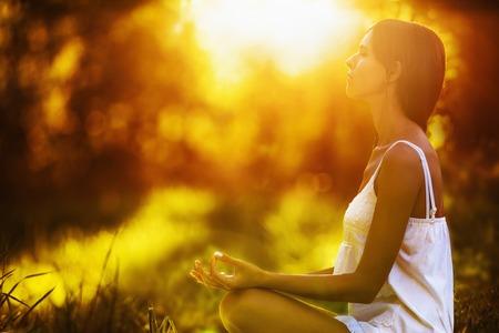 43960890 - yoga woman meditating at sunset. female model meditating in serene harmony