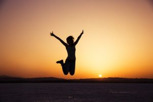 37046532 - silhouette of happy woman jumping in sunset