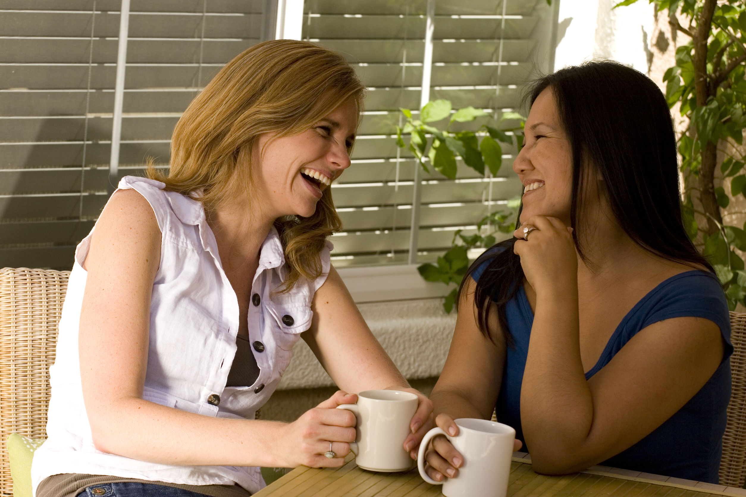 Two women having coffee laughing