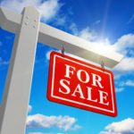 For sale sign against blue sky