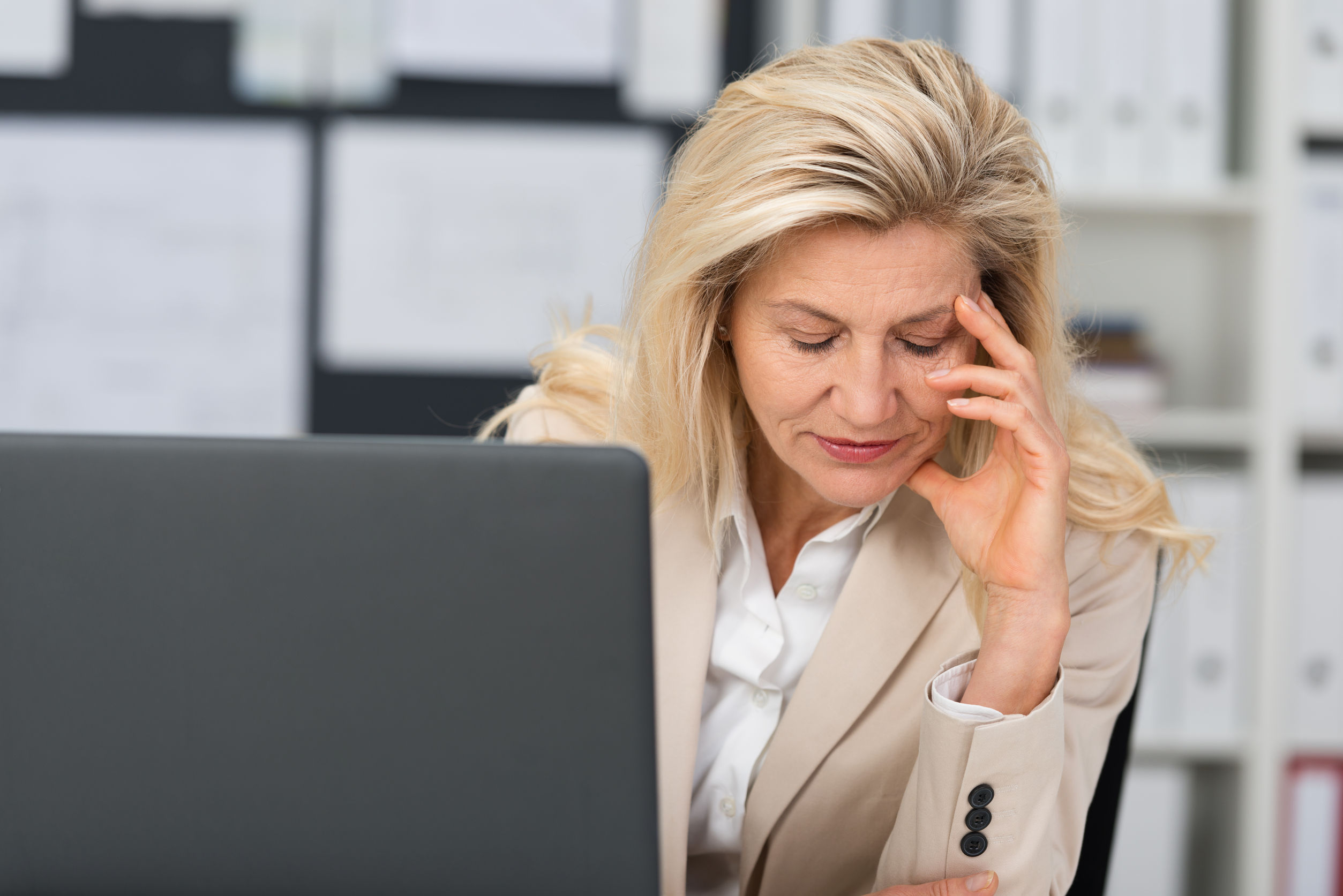 middle-aged businesswoman suffering a stress headache sitting at her desk