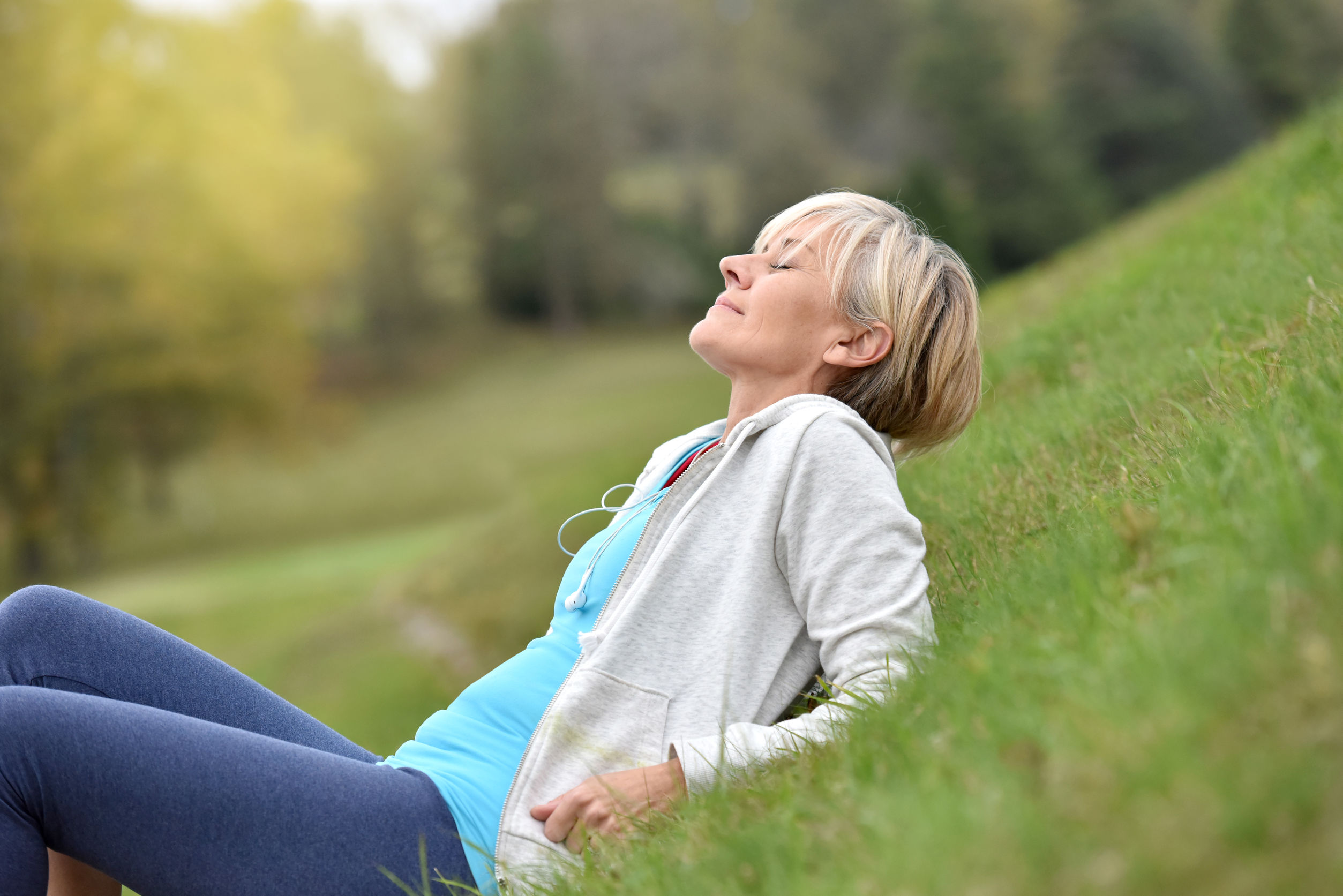 woman lying in field breathing deeply