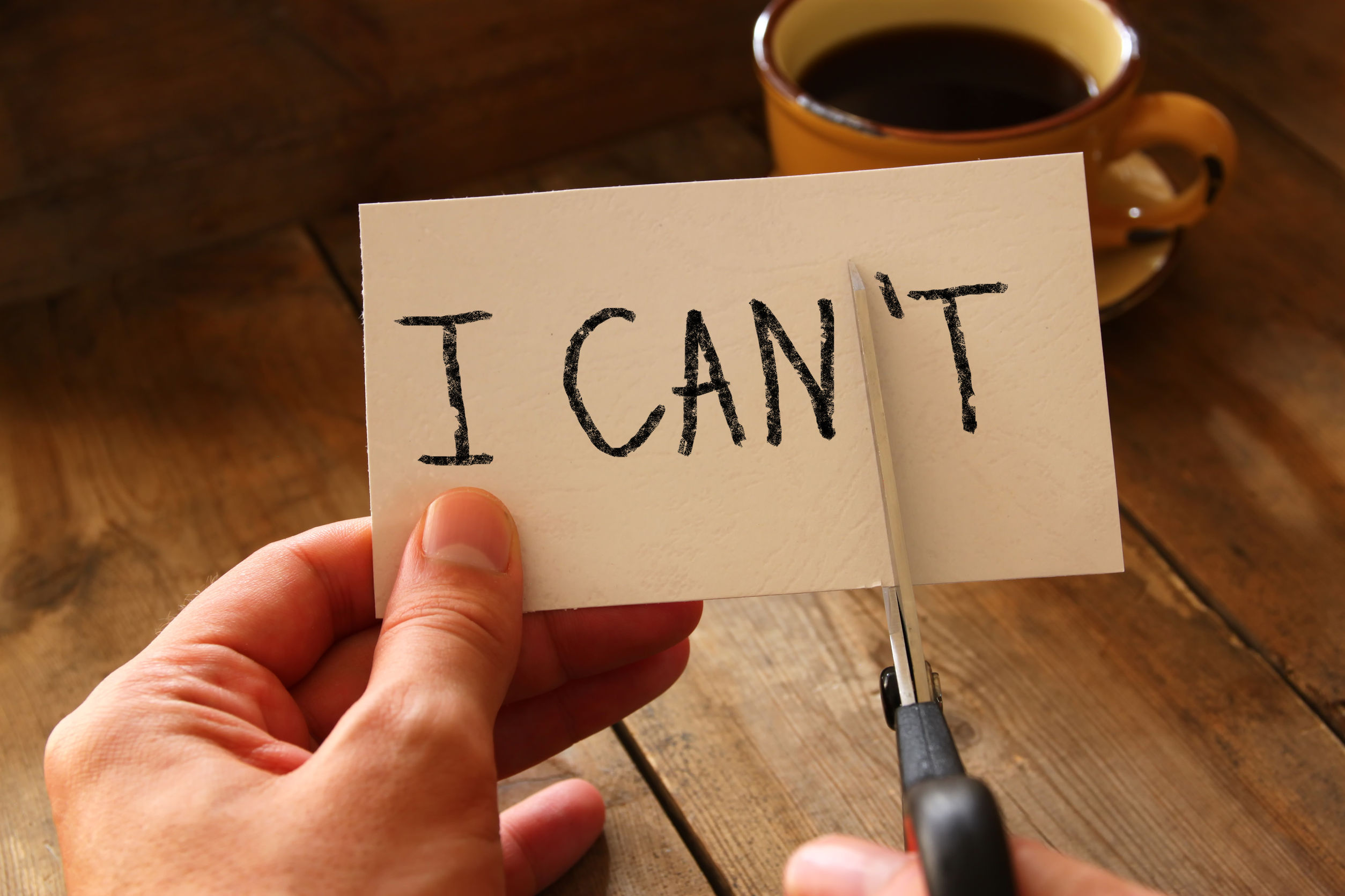 "hands cutting card that says ""I can't"""