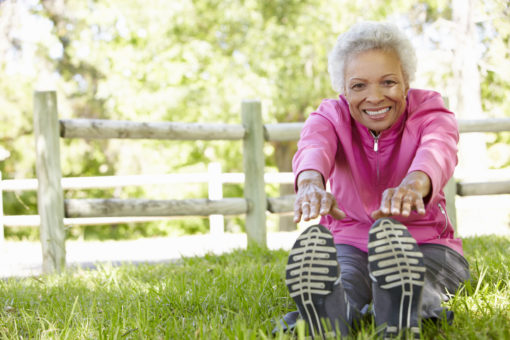 Mature woman stretching in grass