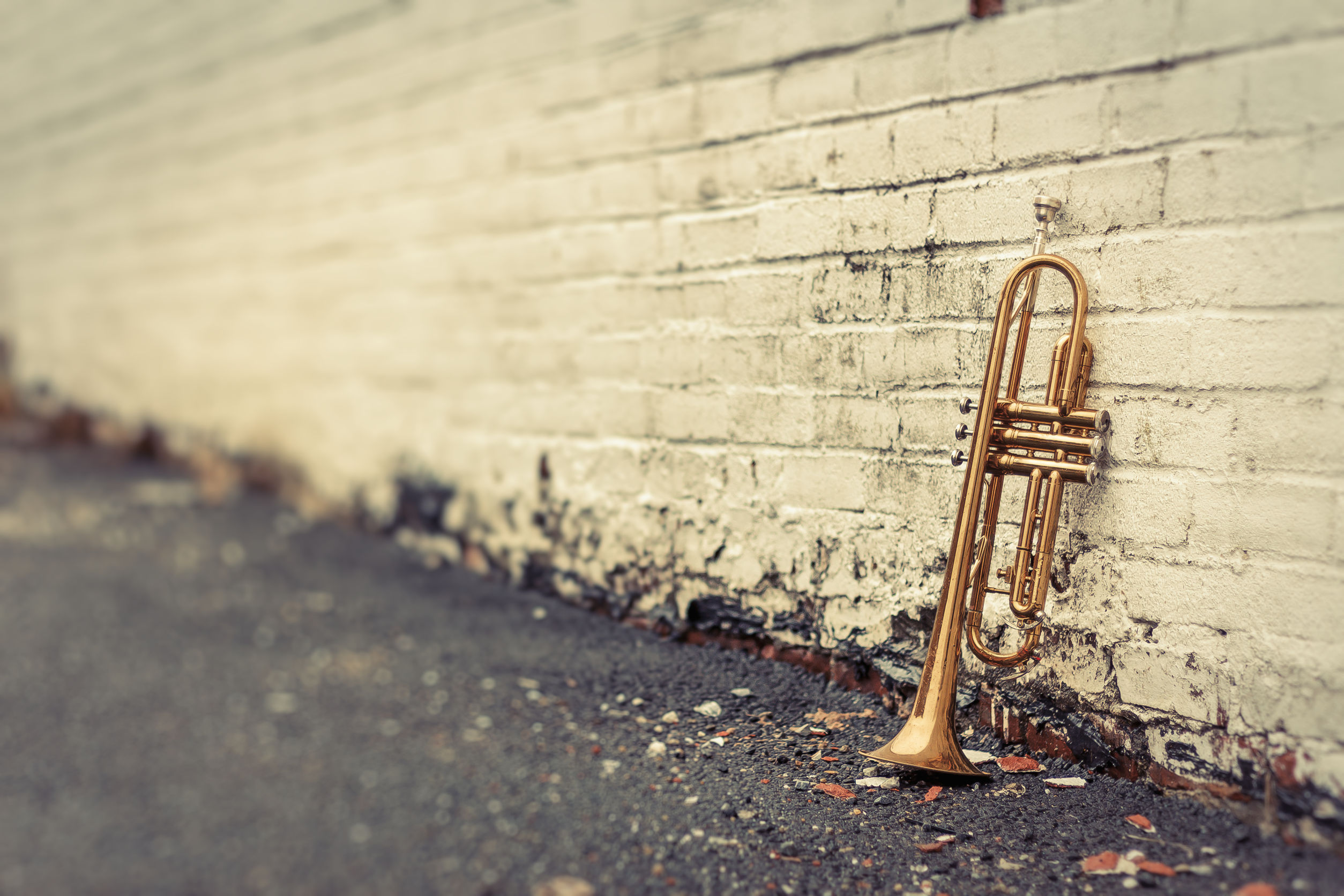 worn trumpet against brick wall