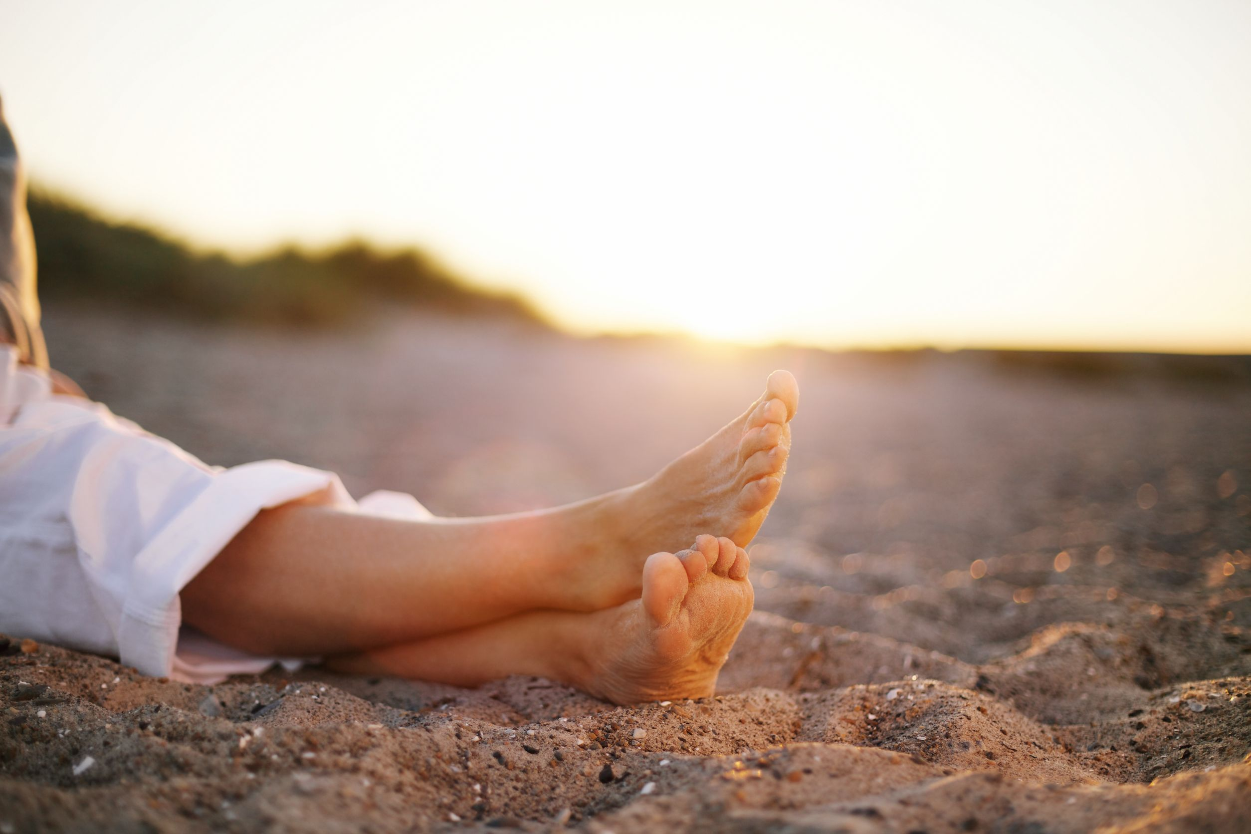 woman's legs crossed on sandy beach