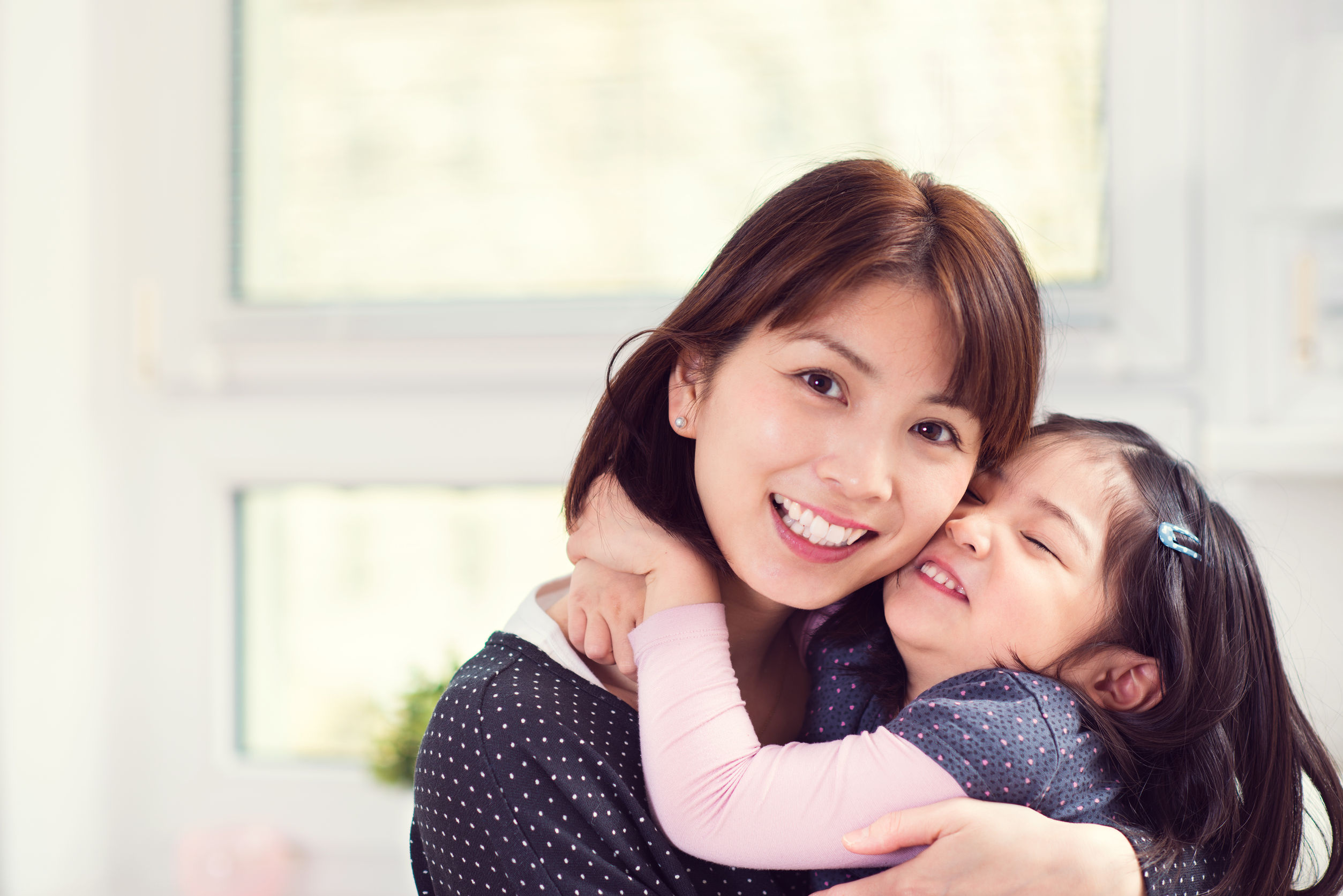 portrait of happy japanese mother hugging with young daughter at home