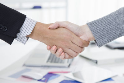 Man and woman formally shaking hands office setting