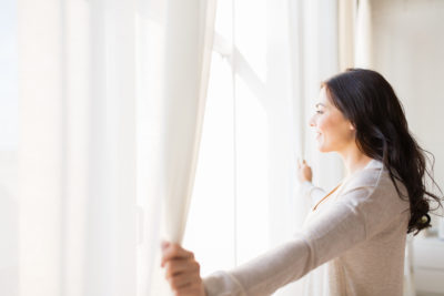woman opening curtains to window looking into sun