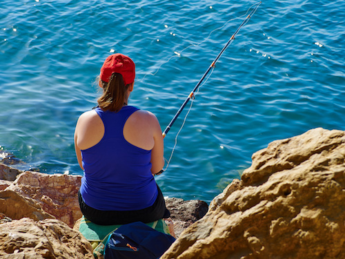 Great leisure activity - Young woman fishing by the ocean sea