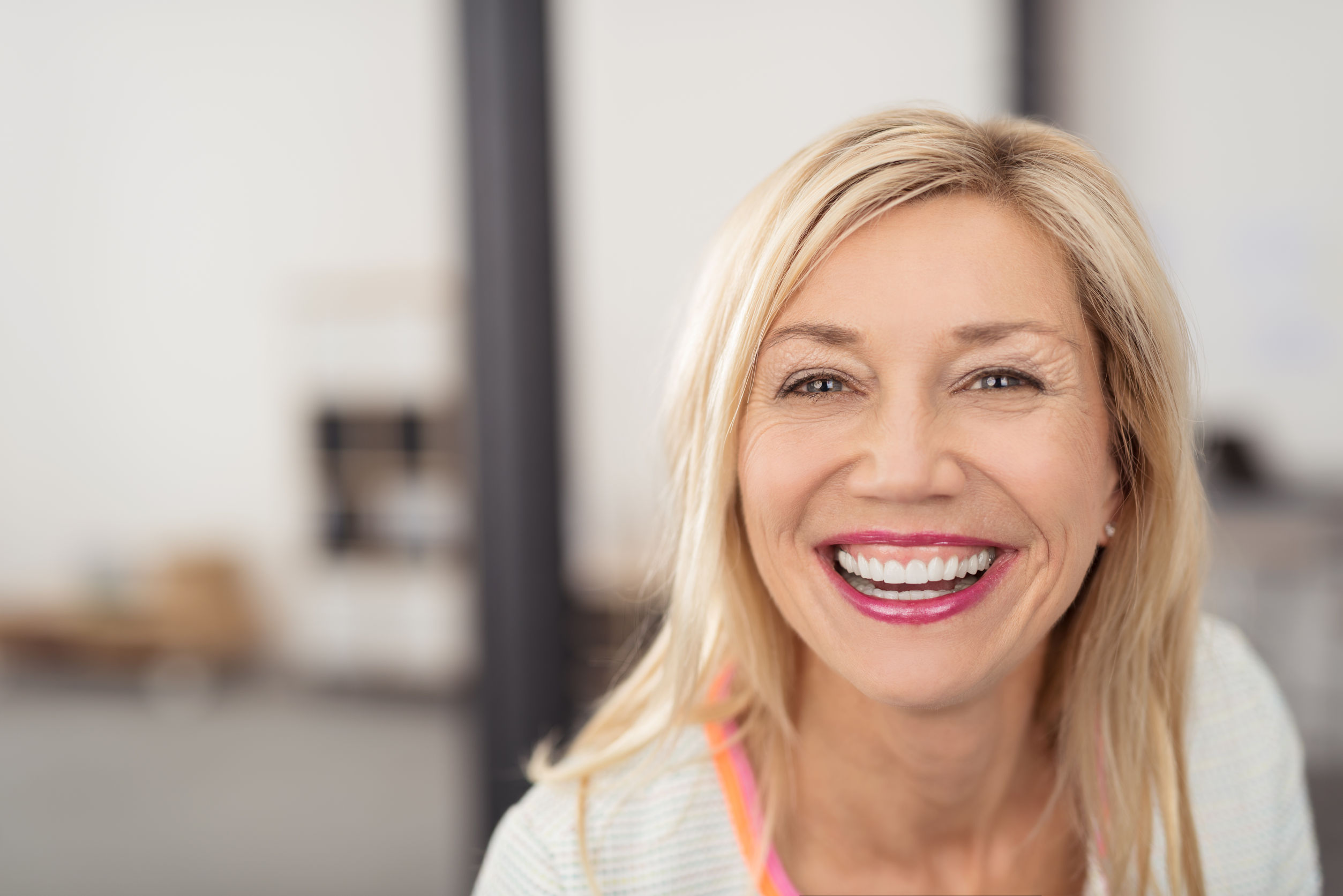 laughing middle-aged blond woman with beaming smile looking directly into the camera