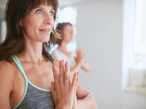 Close up shot of happy mature woman doing yoga looking away smiling. Women in yoga pose vrikshasana using Namaste.