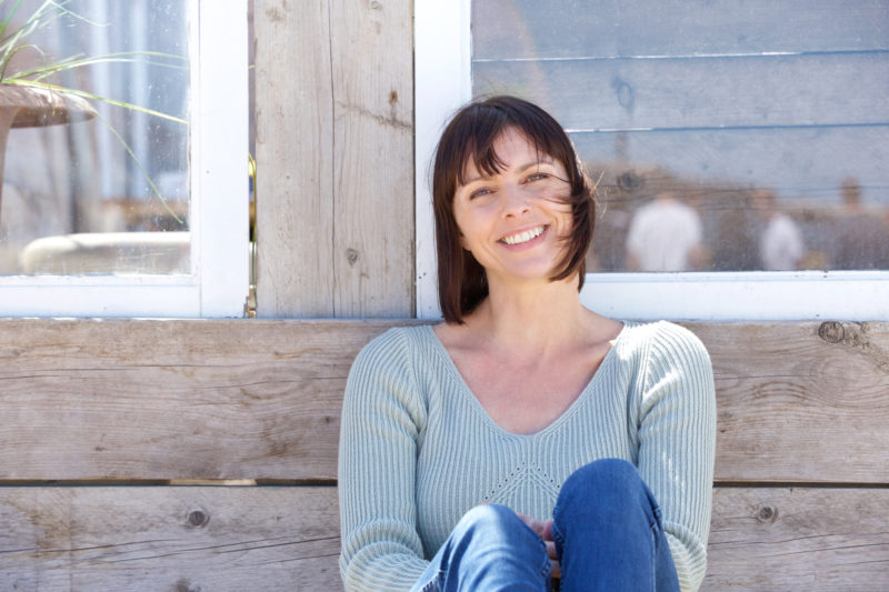 Close up portrait of a happy middle aged woman smiling outdoors