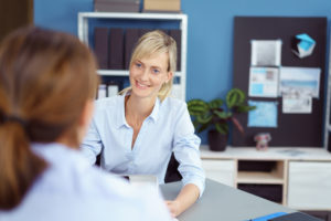 Attractive young woman in a business interview for a job vacancy listening attentively to the female interviewer with a smile, over the shoulder view
