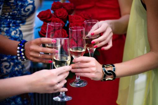 women clinking glasses at happy hour