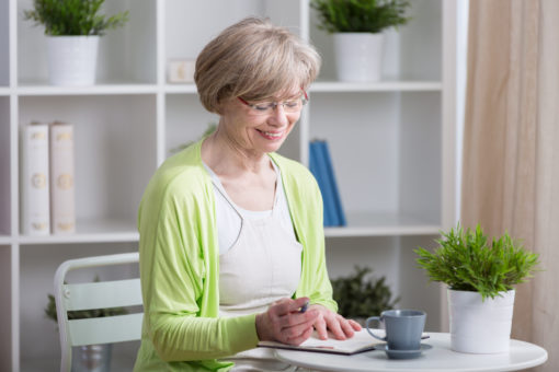 Happy middle aged woman sitting at the table